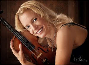 Photo of Ilana Blumberg Thomas holding her violin